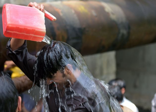 A Pakistani man cools himself off with water collected from a leaking supply line on a hot summer day...