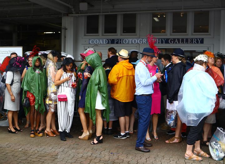 Horse racing fans seek shelter from the rain at Saturday's race.