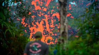 A man watches as lava is seen coming from a fissure in Leilani Estates subdivision on Hawaii's Big Island on May 4, 2018. - Up to 10,000 people have been asked to leave their homes on Hawaii's Big Island following the eruption of the Kilauea volcano that came after a series of recent earthquakes. (Photo by FREDERIC J. BROWN / AFP)        (Photo credit should read FREDERIC J. BROWN/AFP/Getty Images)