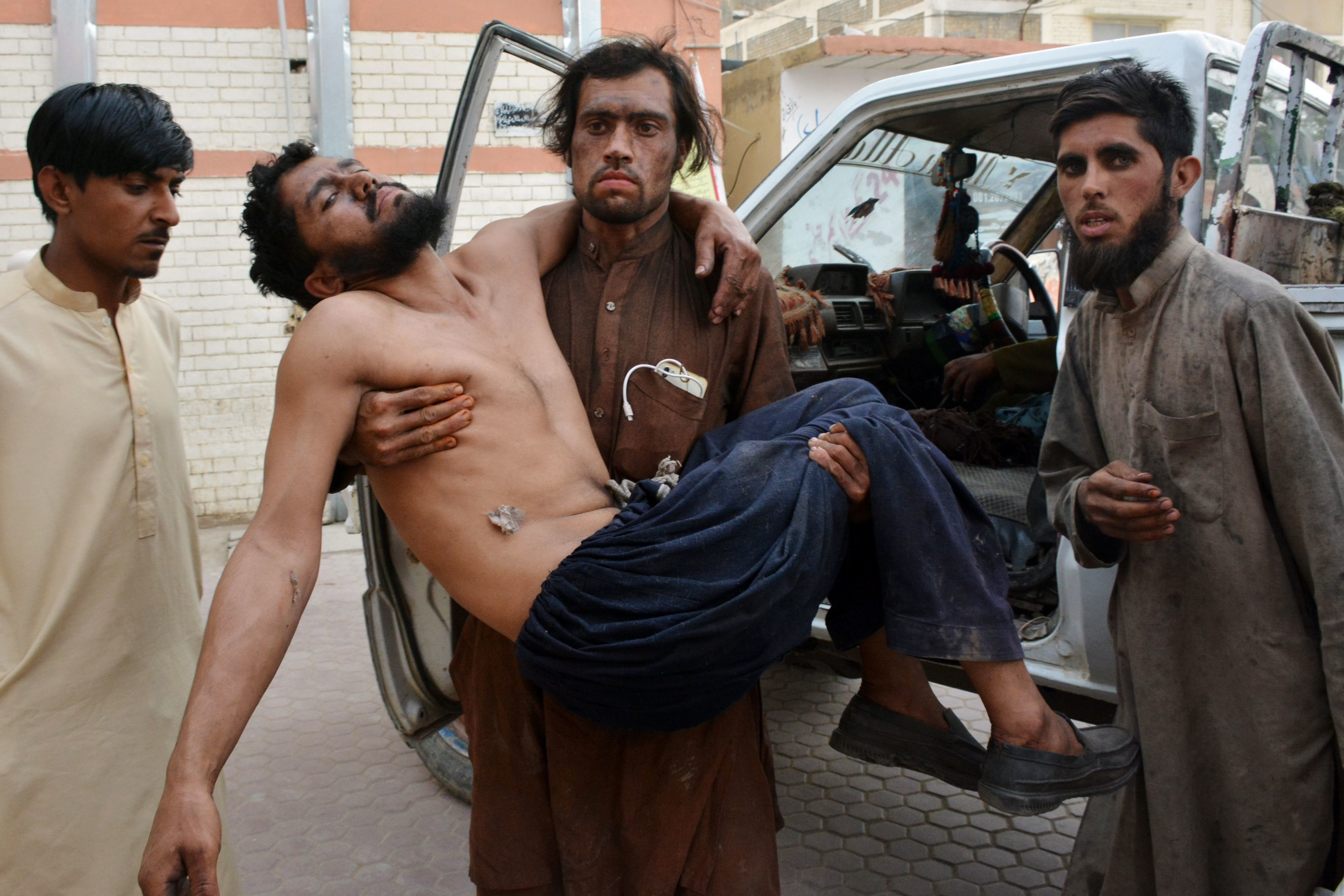 Pakistani miners carry an injured colleague to the hospital after the collapse of coal mine in Quetta on May 5, 2018. - Sixteen miners were killed and nine others were wounded on May 5 when a coal mine collapsed due to a gas explosion in southwestern Pakistan, officials said. (Photo by BANARAS KHAN / AFP)        (Photo credit should read BANARAS KHAN/AFP/Getty Images)
