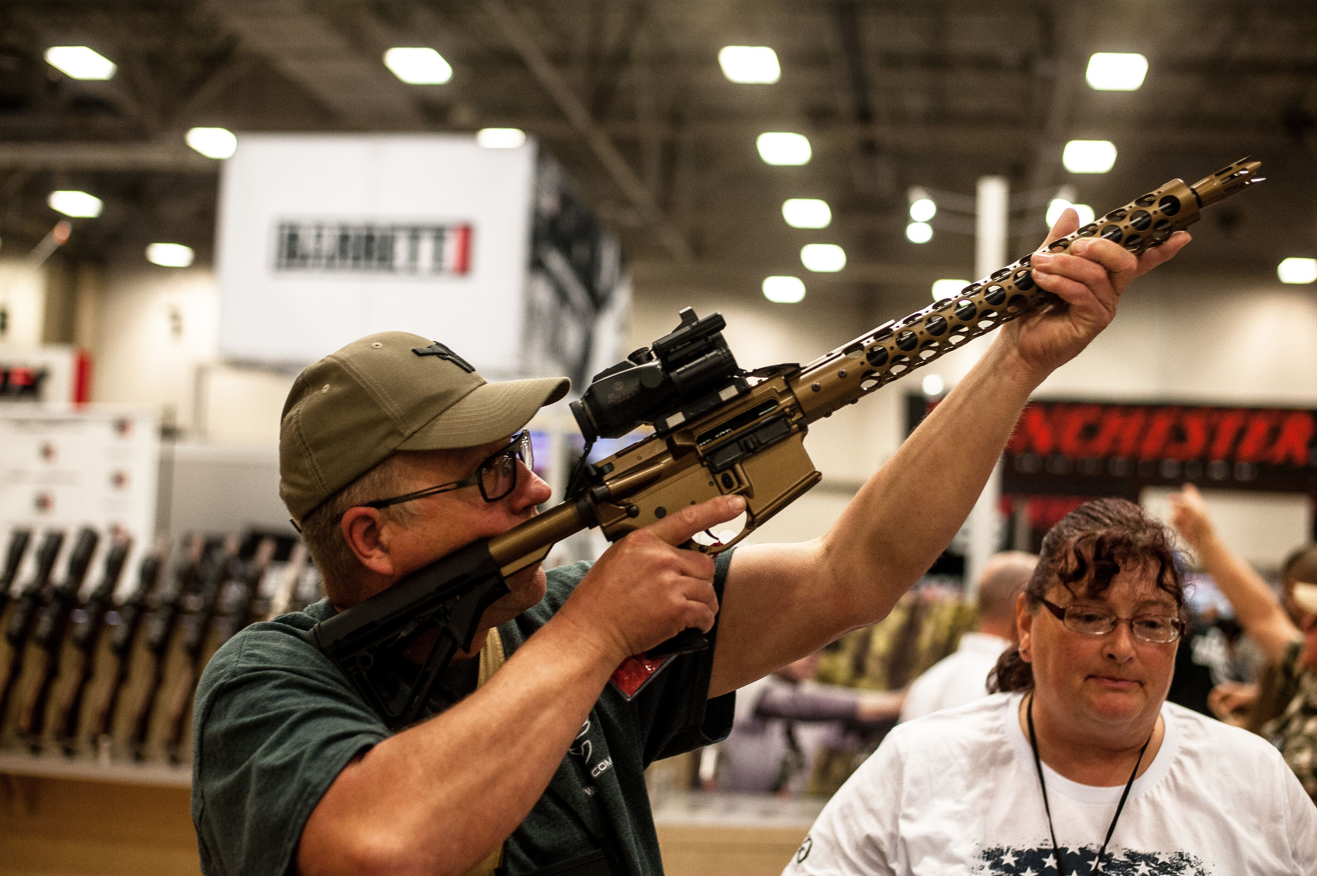 Tim Oelklaus of Missouri holds up a display rifle on the expo floor of the annual NRA meeting in Dallas, TX on May 4, 2018.