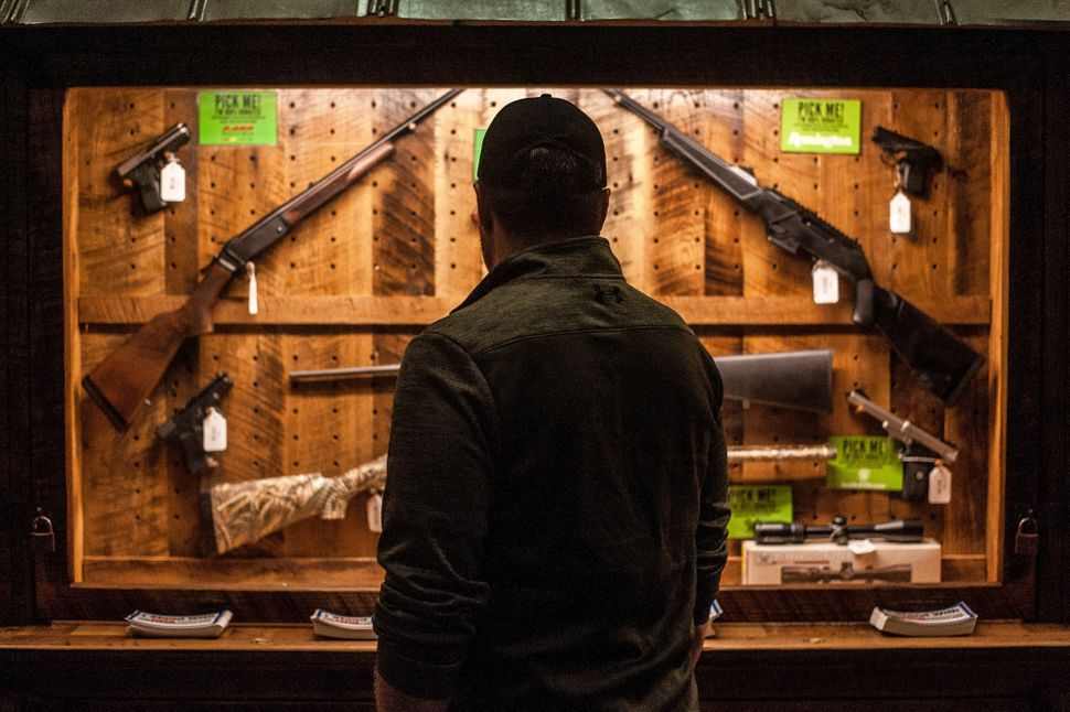 A man looks at a gun display on the first day of the NRA's annual meeting in Dallas.