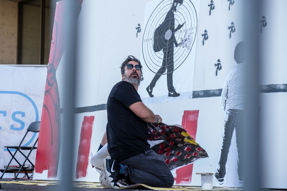 Manuel Oliver, whose son, Joaquin, was killed at the school shooting in Parkland, Florida, this year, creates a mural at the