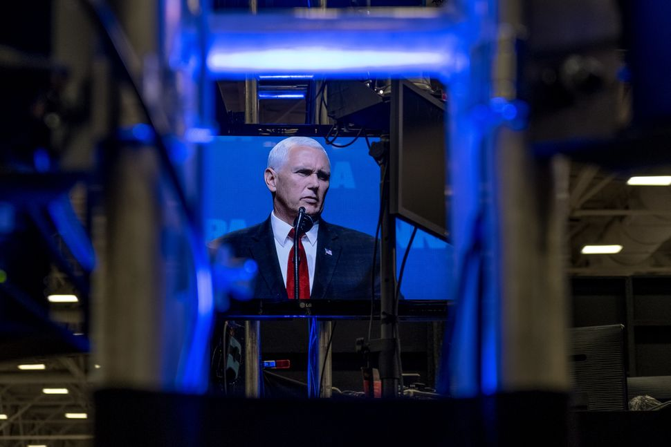A television screen on the expo floor shows a live feed of Vice President Mike Pence's speech on the first day of the event.