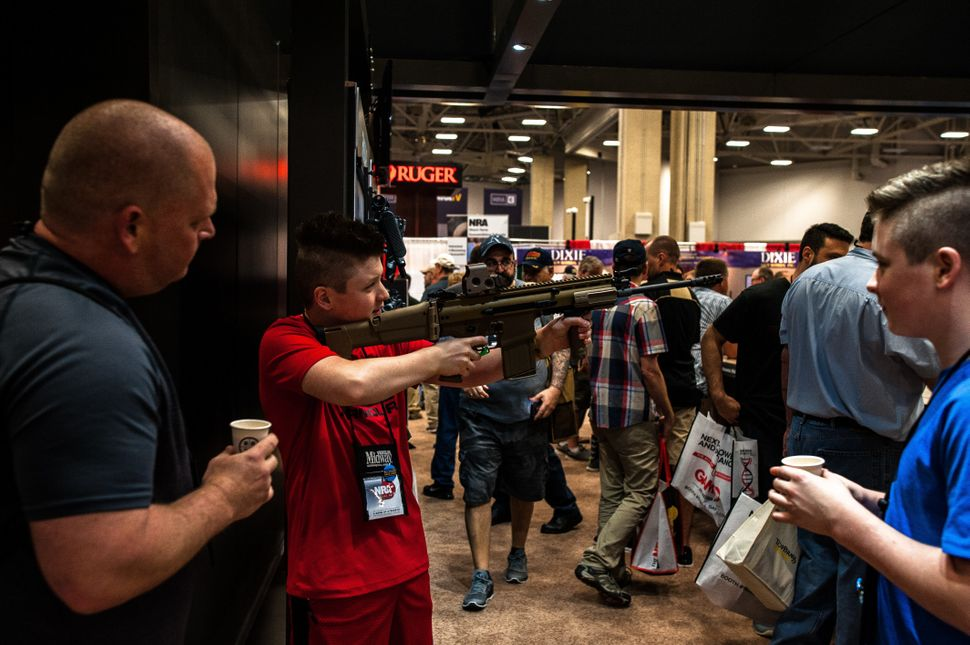A local Dallas family passes around a rifle on the expo floor Friday.