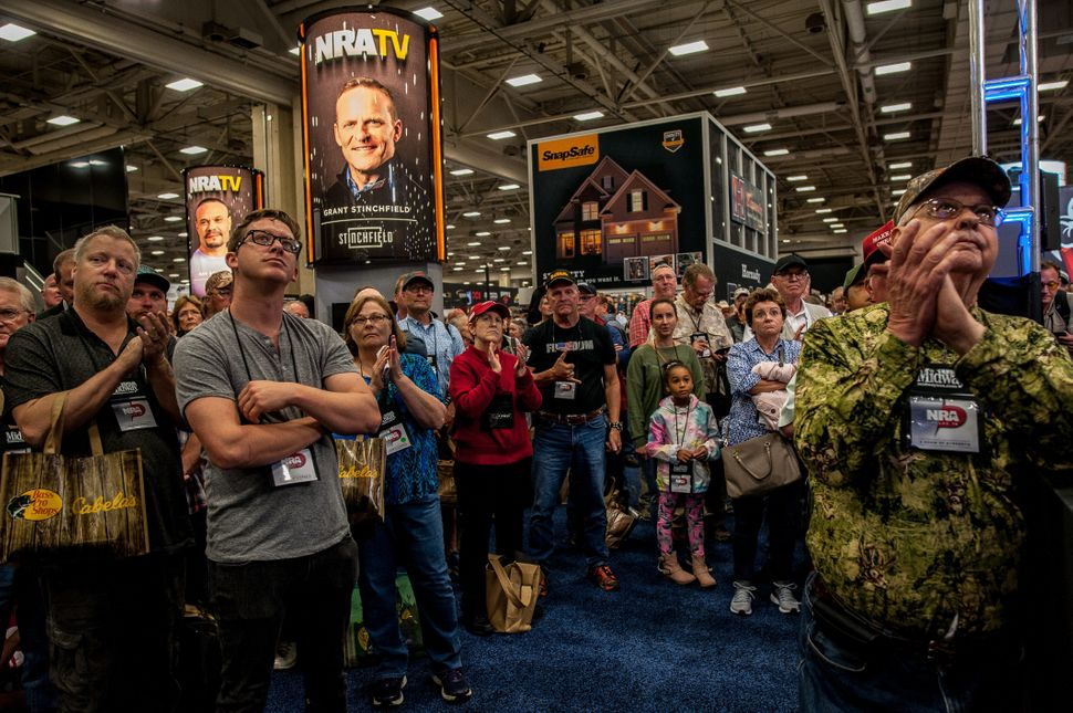A crowd watches a screen showing a live feed of President Trump's speech at the NRA annual meeting on May 4.