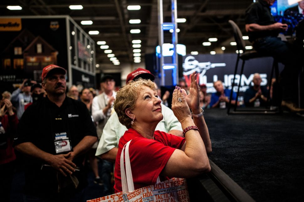 A woman claps in response to a speech by Trump as she watches a live feed of the event on the expo floor Friday.