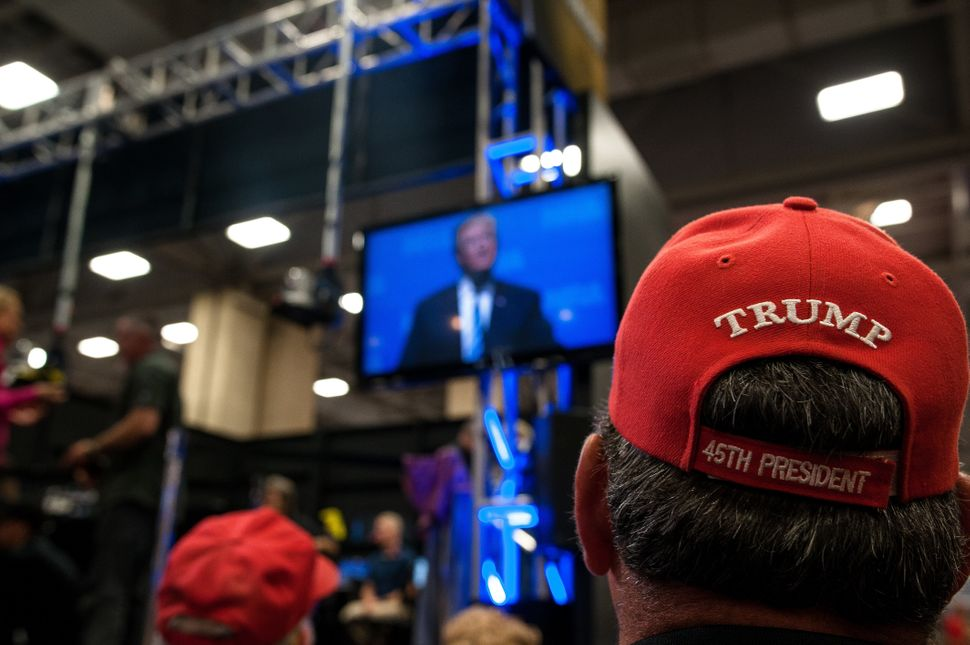 A crowd watches a screen showing a live feed of Trump's speech onFriday.