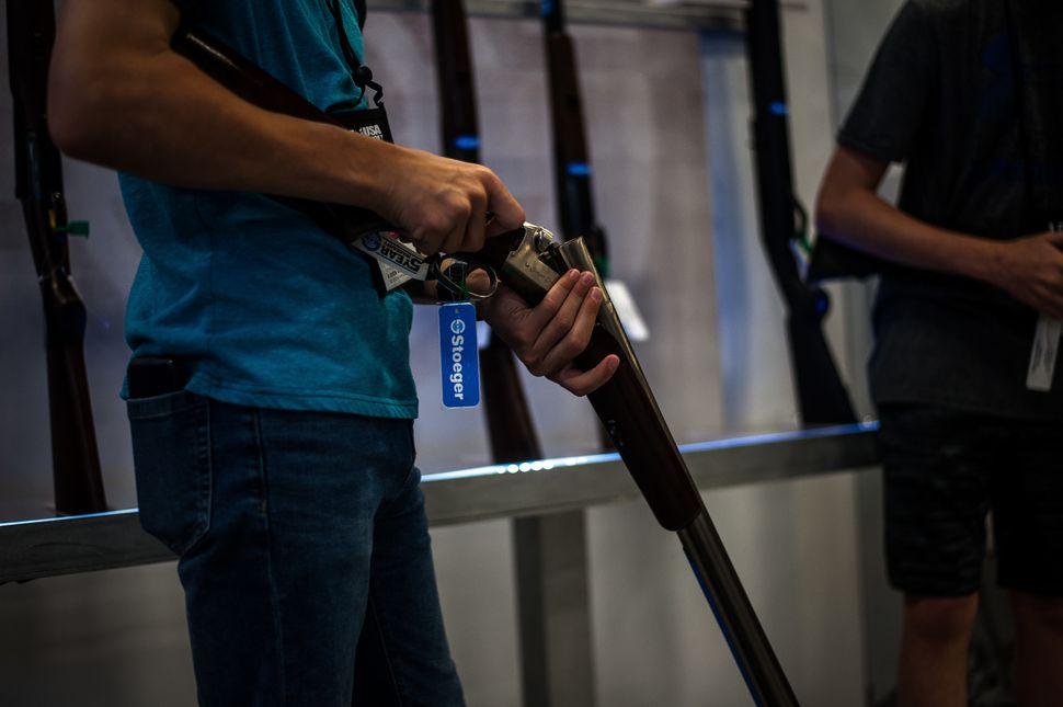 Slade Jamieson, of Keller, Texas, examines a gun on the expo floor Saturday.