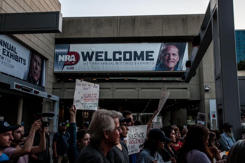 Protesters march to the Kay Bailey Hutchison Convention Center, where the NRA is holding its annual meeting, onFriday.