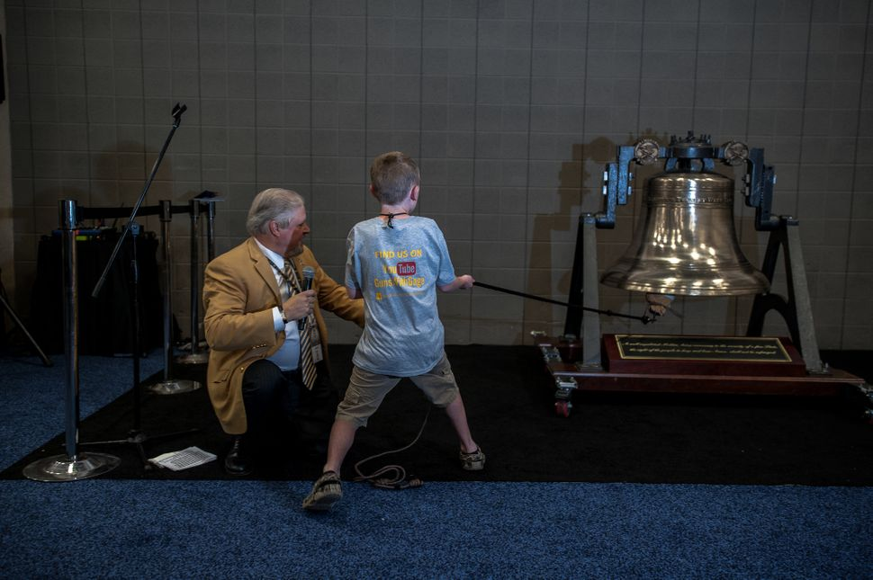 """A young boy yells, """"Let freedom ring,"""" as he rings a replica of the Liberty Bell on the expo floor onSunday."""