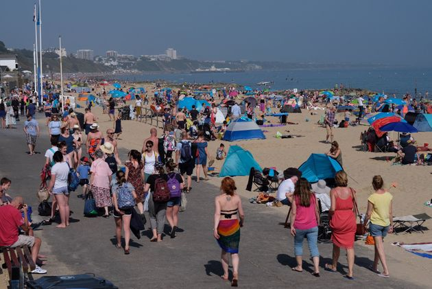 People enjoying the sunshine at Branksome Beach, Poole.