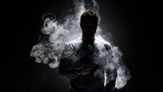 Smoke fragments on a black background.Young smoker is vaping e-cigarette or vaporizer.