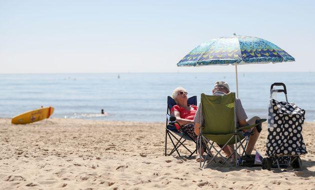 People enjoy the warm weather on Boscombe beach in Dorset.