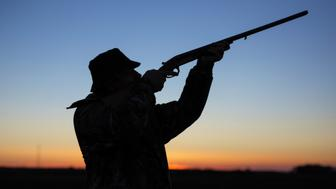 Hunter's silhouette at sunset with gun in his hands