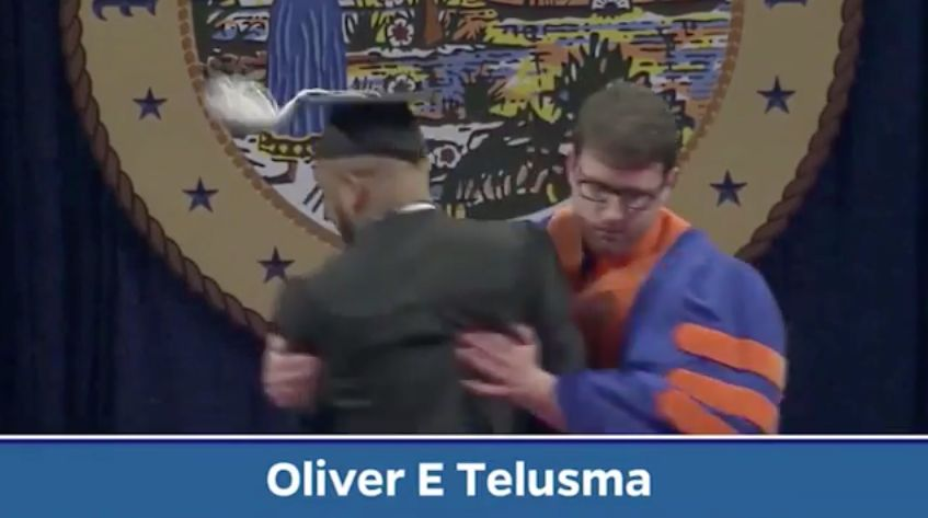 A University of Florida graduate is pulled off stage for dancing during the commencement ceremony