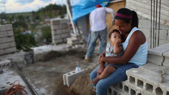 SAN ISIDRO, PUERTO RICO - DECEMBER 23:  Mother Isamar holds her baby Saniel, 9 months, as husband Samuel mixes cement at their makeshift home, under reconstruction, after being mostly destroyed by Hurricane Maria, on December 23, 2017 in San Isidro, Puerto Rico. Their neighborhood remains without electricity. Barely three months after Hurricane Maria made landfall, approximately one-third of the devastated island is still without electricity. While the official death toll from the massive storm remains at 64, The New York Times recently reported the actual toll for the storm and its aftermath likely stands at more than 1,000. A recount was ordered by the governor as the holiday season approached.  (Photo by Mario Tama/Getty Images)