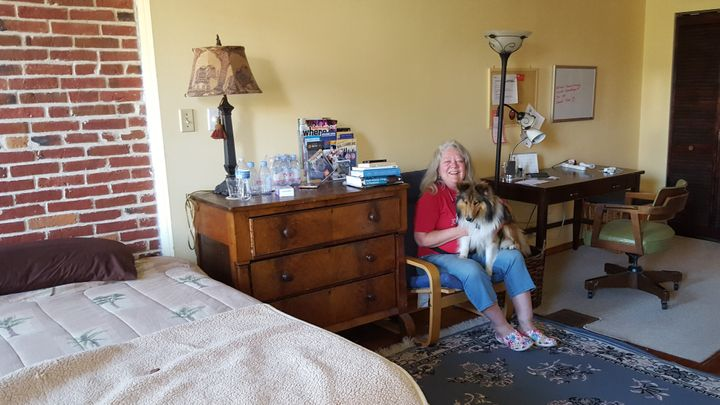 Baltimore resident Jeannette Belliveau, who rents a couple of rooms in her historic townhouse to short-term guests, sits with