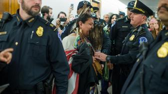UNITED STATES - JANUARY 18: Joann Spotted Bear, from Wounded Knee, S.D., is arrested by Capitol Police after protesting the Dakota Access Pipeline outside of the Senate Environment and Public Works Committee confirmation hearing for Scott Pruitt, President-elect Trump's nominee to be administrator of the Environmental Protection Agency, in Dirksen Building, January 18, 2017. (Photo By Tom Williams/CQ Roll Call)
