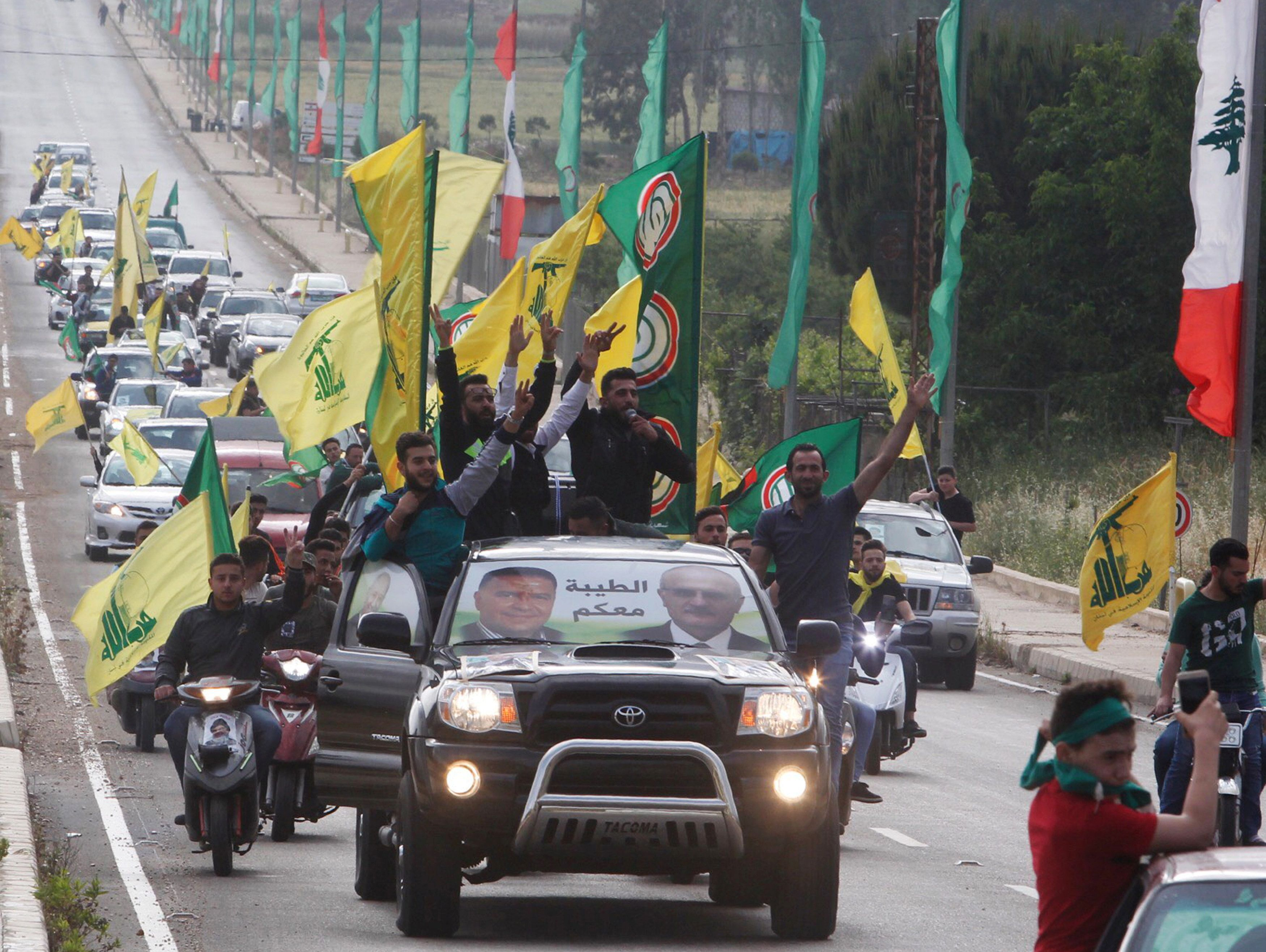 Supporters of Lebanon's Hezbollah and Amal Movement gesture as they ride in a car in Marjayoun, Lebanon May 7, 2018.