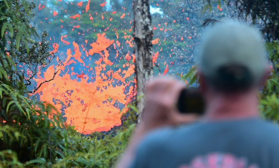 A man watches as lava spews from a fissure in Leilani Estates on Friday.