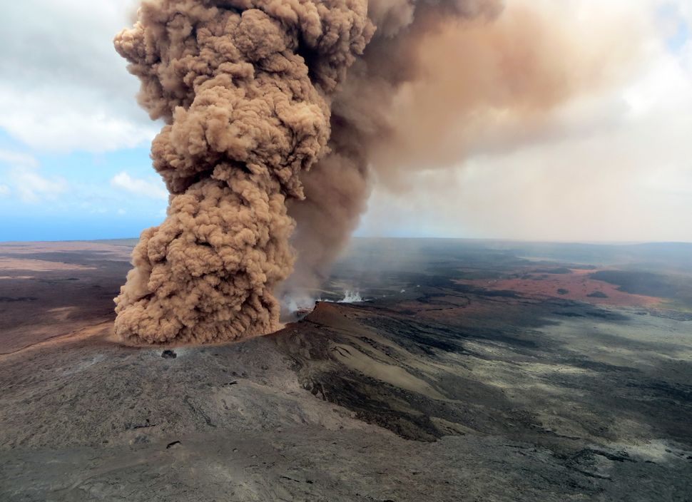 A column of robust, reddish-brown ash plume looms over the Big Island on Friday.
