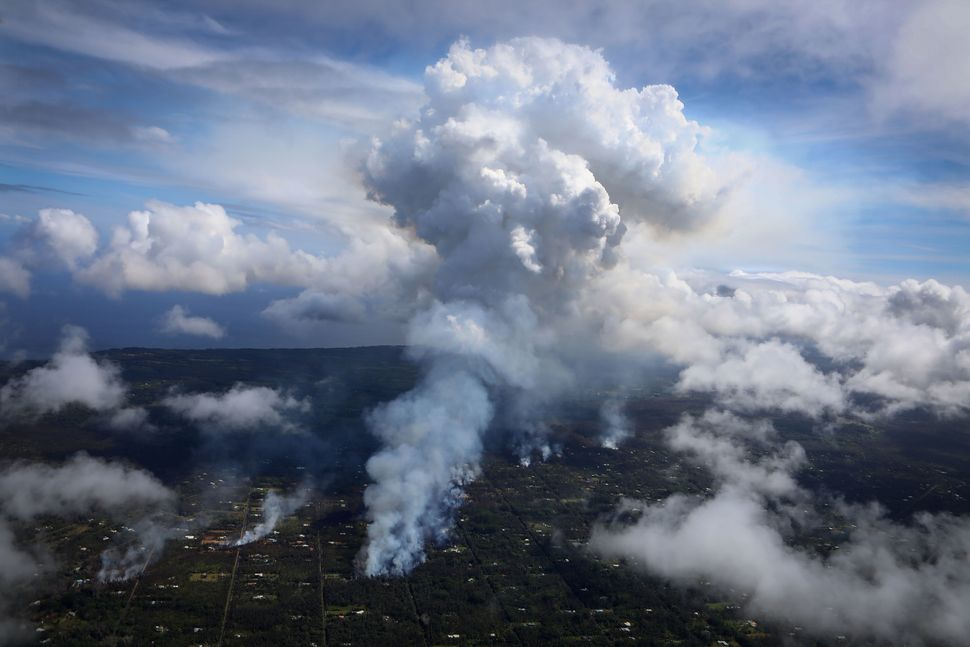 A plume of gas mixed with smoke from fires caused by lava rises amid clouds in Leilani Estates on Sunday.