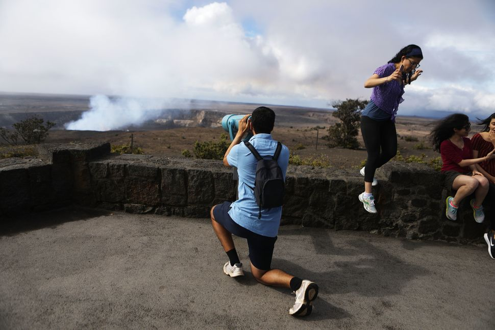 Visitors view the Halemaumau crater within the Kilauea volcano summit caldera at the re-opened Hawaii Volcanoes National Park