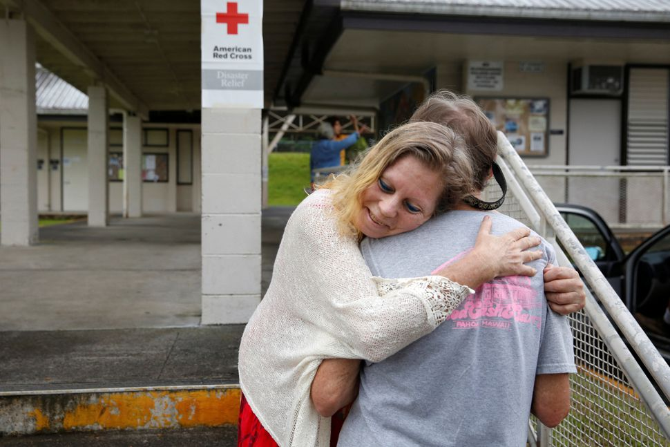 Carolyn McNamara, 70, hugs her neighbor Paul Campbell, 68, at an evacuation center in Pahoa after moving out of their homes i