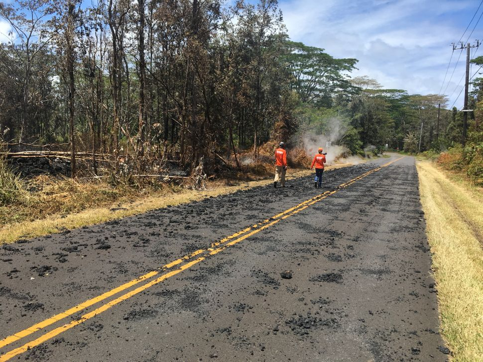 U.S. Geological Survey scientists monitor Kilauea's eruption spatter on the roads in Leilani Estates on Sunday.