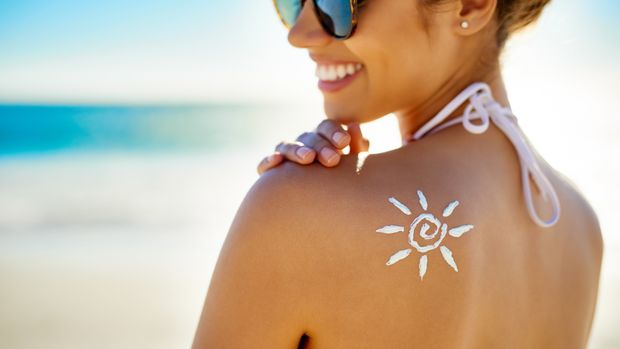 Cropped shot of a young woman posing with suntan lotion on her shoulder