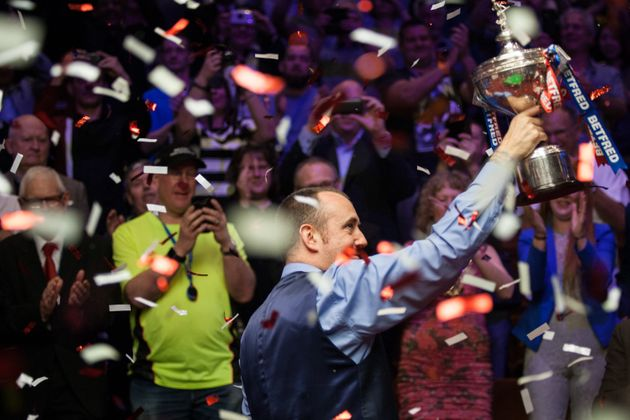Williams holds his trophy aloft after beating John Higgins