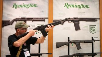 A man aims a Remington firearm at the annual National Rifle Association (NRA) meeting in Dallas, Texas, U.S., May 4, 2018. REUTERS/Adrees Latif