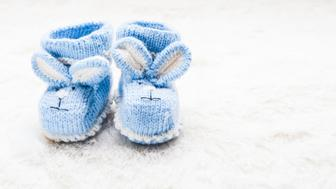 Knitted blue baby booties with rabbit muzzle for little boy