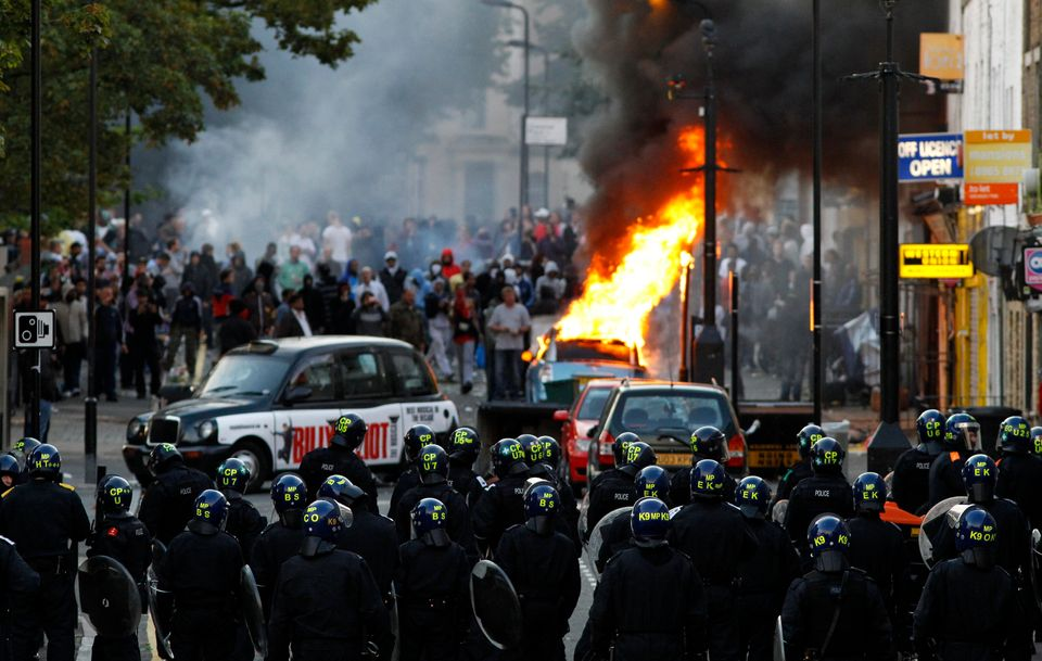 Police officers in riot gear block a road near a burning car on a street in Hackney, east London August...