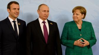 German Chancellor Angela Merkel poses with French President Emmanuel Macron (L) and Russia's President Vladimir Putin (C) prior to a meeting during the G20 summit in Hamburg, northern Germany, on July 8, 2017. Leaders of the world's top economies gather from July 7 to 8, 2017 in Germany for likely the stormiest G20 summit in years, with disagreements ranging from wars to climate change and global trade. / AFP PHOTO / POOL / Carsten Rehder        (Photo credit should read CARSTEN REHDER/AFP/Getty Images)