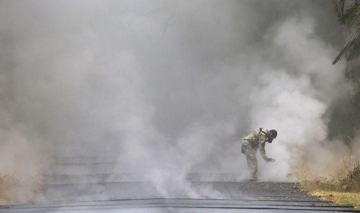 U.S. Army National Guard 1st Lt. Aaron Hew Len takes measurements for sulfur dioxide gas at volcanic fissures in Leilani