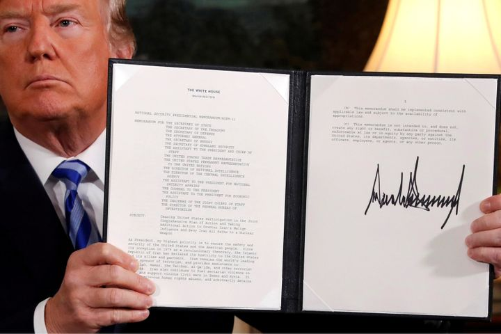 Trump holds up a proclamation declaring his intention to withdraw from the JCPOA Iran nuclear agreement after signing it in t
