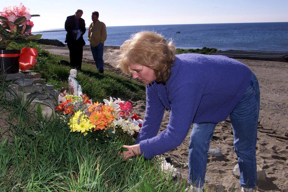 Helen McKendry lays flowers on Templetown beach in Co Louth, Irish Republic during a search for...