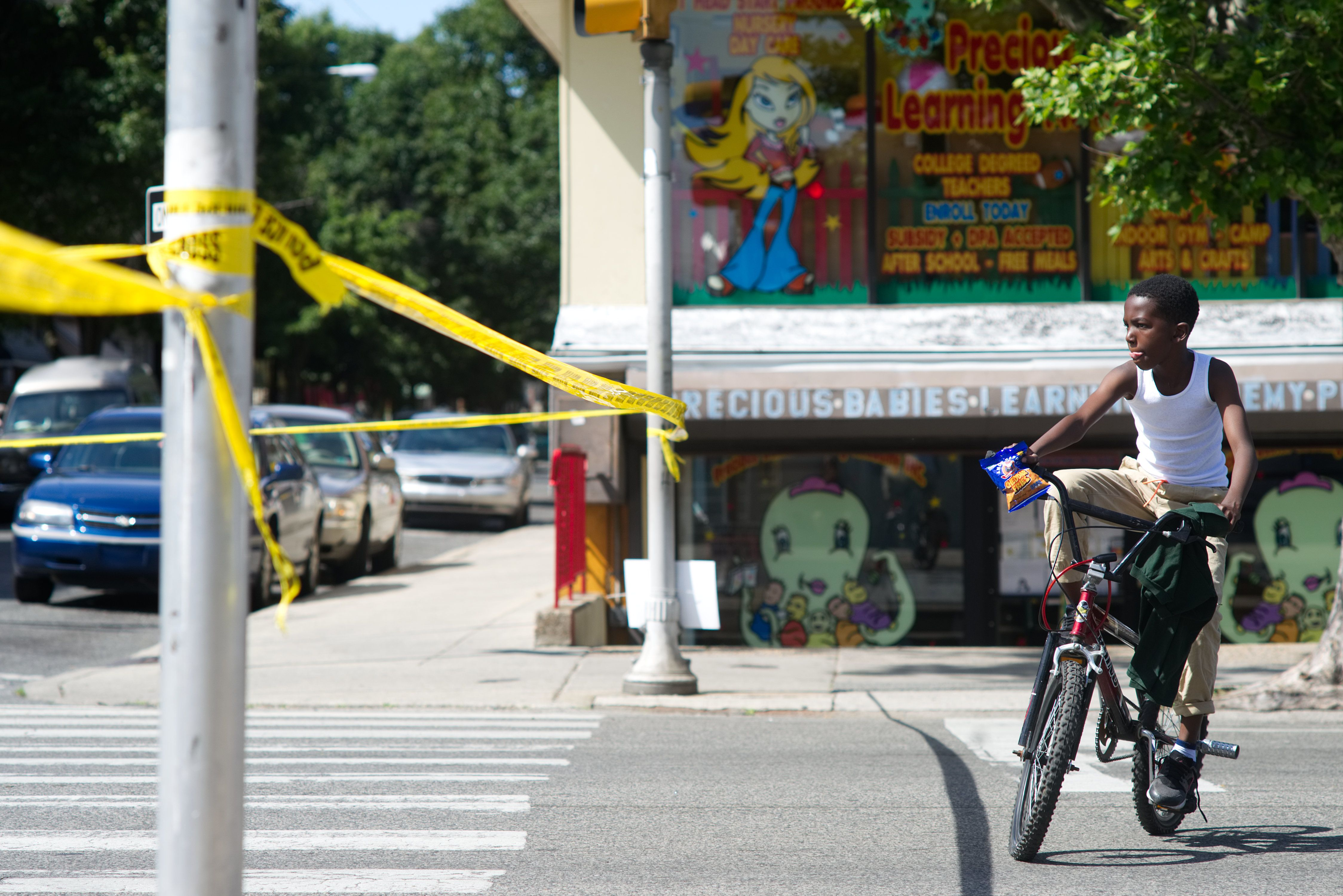 An African-American boy circles on a BMX bike near the site of a crime investigation after a shooting, in North Philadelphia, PA, on June 10, 2016. Teenagers on stunt bikes are described as 'Wheelie Kids' and are a growing subcultural phenomenon, often appearing in a flash mob style at or near large protest gatherings in Philadelphia. (Photo by Bastiaan Slabbers/NurPhoto via Getty Images)