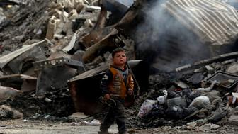 A Syrian child walks past the debris of destroyed buildings in the northern Syrian city of Raqa, on January 11, 2018 after a huge military operation led on the ground by Kurdish fighters and in the air by US warplanes defeated jihadists from the Islamic State group but also left the city completely disfigured. Once home to around 300,000 people, Raqa's neighbourhoods were empty when it was declared retaken in mid-October. Three months on, despite the lack of infrastructure and the lingering threat of unexploded mines and bombs, a trickle of residents -- a few hundred families -- are attempting to return.  / AFP PHOTO / DELIL SOULEIMAN        (Photo credit should read DELIL SOULEIMAN/AFP/Getty Images)