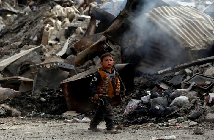 A Syrian child walks past destroyed buildings in the northern Syrian city of Raqa, on January 11, 2018, after a huge military
