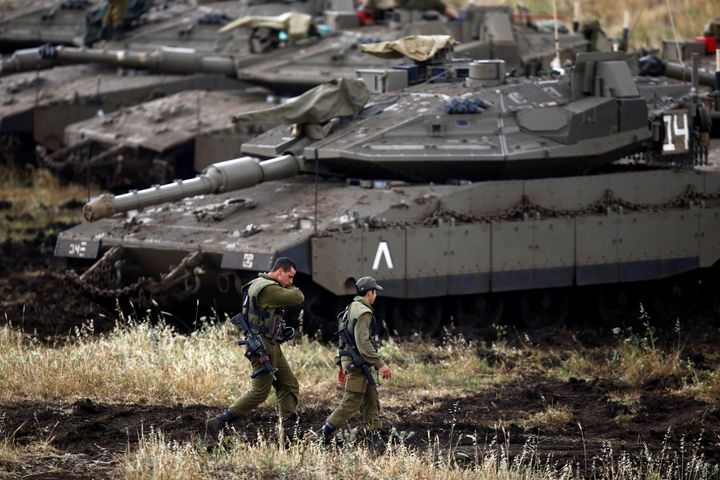 Israeli soldiers walk next to tanks near the Israeli side of the border with Syria in the Israeli-occupied Golan Heights, Isr