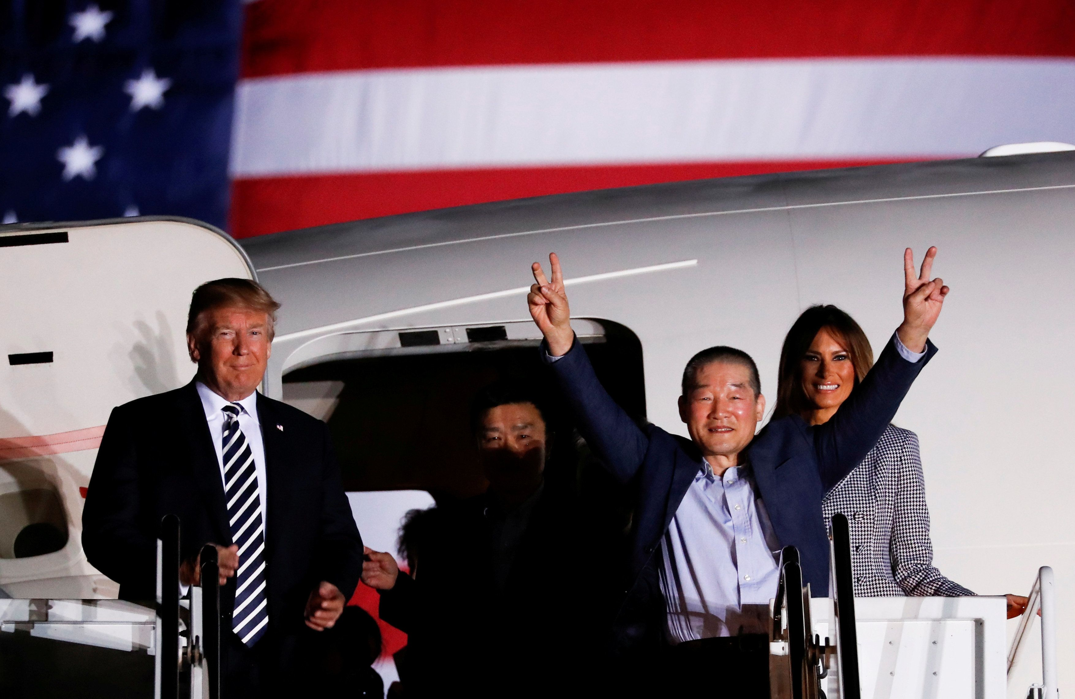 One of the Americans formerly held hostage in North Korea gestures next to U.S.President Donald Trump and first lady Melania Trump, upon their arrival at Joint Base Andrews, Maryland, U.S., May 10, 2018.  REUTERS/Jonathan Ernst