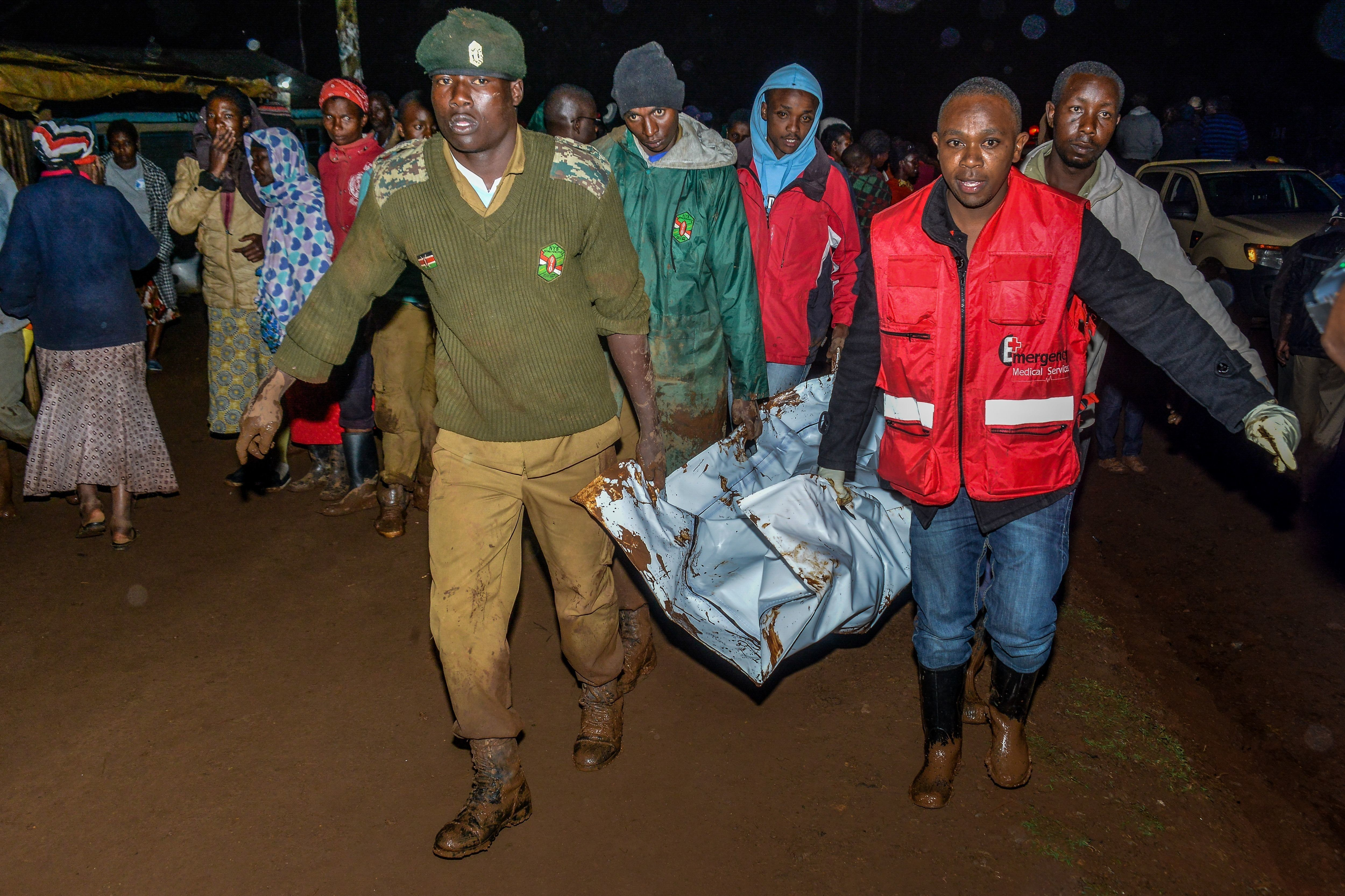 People carry a victim's body from a residential area after Patel dam burst its bank at Solai, about 40 kilometres north of Nakuru, Kenya, on May 10, 2018. (Photo by AFP)        (Photo credit should read /AFP/Getty Images)