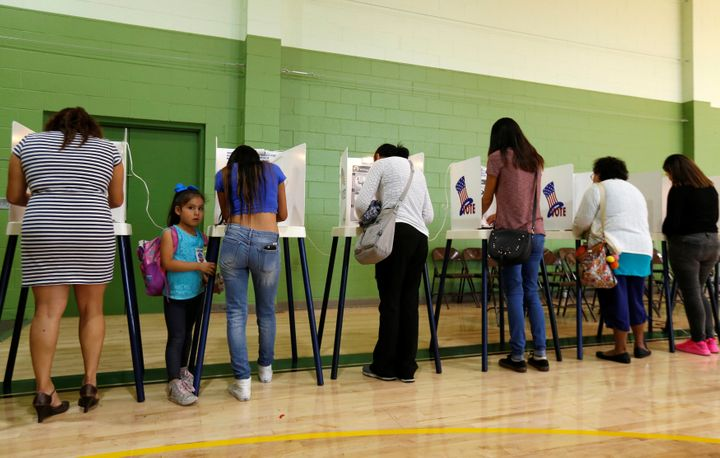 Brisa Silva stands next to her mother, Cinthia Lopez, as she votes at the Evergreen Recreation Center during the presidential election in the Boyle Heights area of Los Angeles on Nov. 8, 2016.