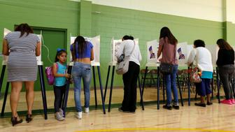 Brisa Silva stands next to her mother Cinthia Lopez as she votes at the Evergreen Recreation Center during the 2016 presidential election in the Boyle Heights area of Los Angeles, California, U.S., November 8, 2016.  REUTERS/Mario Anzuoni