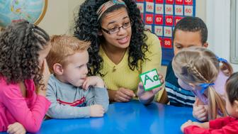 A woman is teaching the letters of the alphabet to her preschool students.
