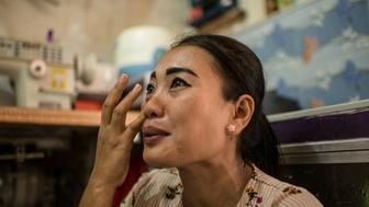 Istiyaroh, 35, is crying inside her tiny rental room, while remembering her two daughters left at her village with her parents. Jakarta, 6th April 2018.