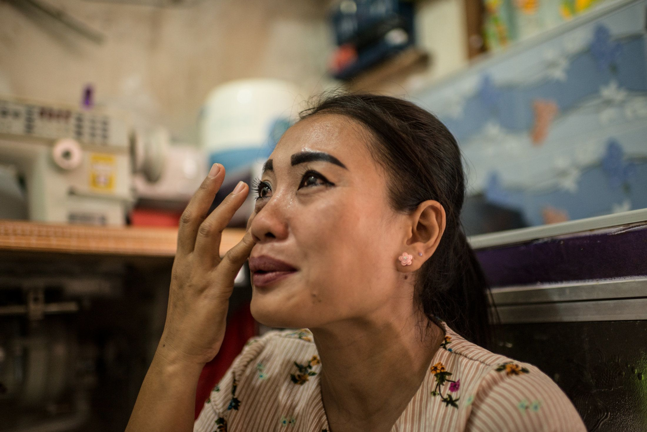 Istiy cries inside her tiny rental room while speaking of the two daughters she left behind in her village.